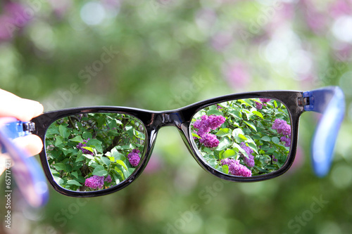 eyeglasses in the hand over blurred background - 65717421