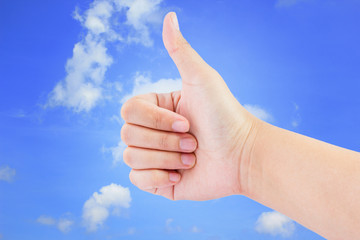 Woman hand with thumb up  on the blue sky background