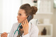 Portrait of medical doctor woman talking phone