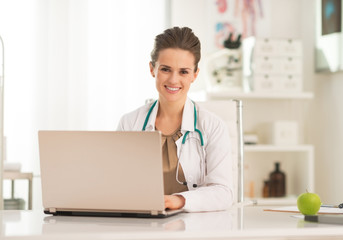 Happy medical doctor woman working on laptop