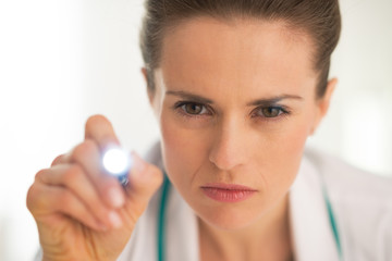 Portrait of medical doctor woman examining using flashlight