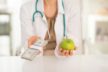 Closeup on medical doctor woman holding apple and money pack