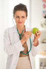 Happy medical doctor woman examining apple with stethoscope