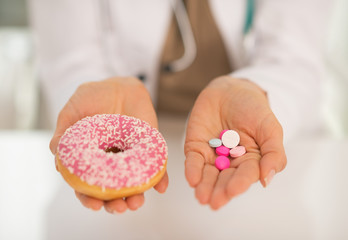 Closeup on medical doctor woman showing donut and pills