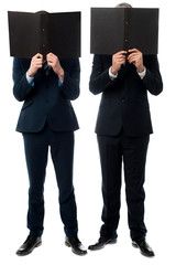 Businessmen hiding their faces with folder