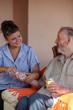 nurse giving medication to senior man