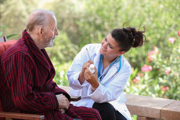Dr or nurse giving medication to senior patient.