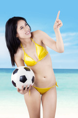 Sexy model with a ball pointing at copyspace
