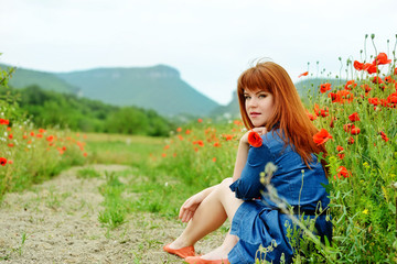 redhead girl in poppy field