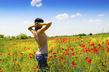 Woman relaxing in a poppy field