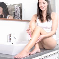 Schöne junge Frau rasiert sich die Beine