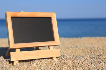 Blank blackboard on the beach