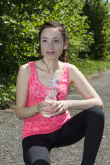 Sporty woman holding a water bottle during a break