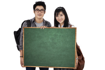 Two student holding empty blackboard 1
