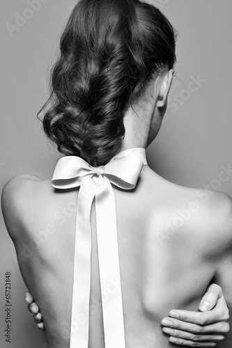 Back of beautiful gentle girl with silk bow on the neck - 65723848
