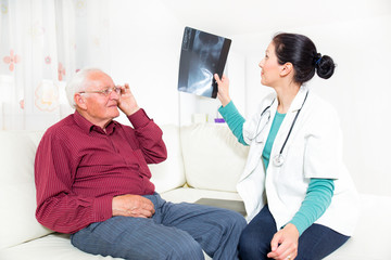 Home Care. Doctor showing x-ray to senior man