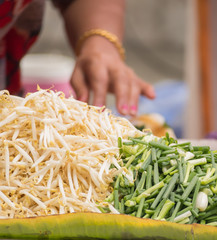 Hand of street vender preparing bean sprouts and scallion for Pa