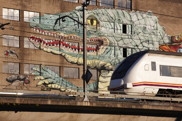 Lizard graffiti on a building facade and train