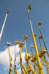 Yellow telescopic cranes under a blue sky