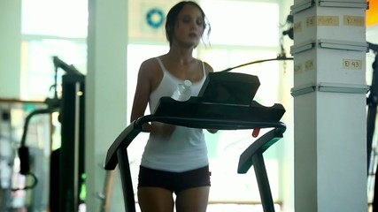 Young woman doing exercises on treadmill, with barbell on bench