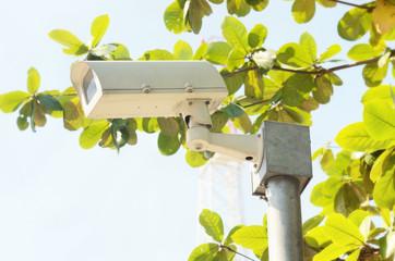 Security cameras against blue sky