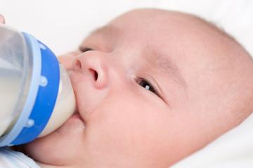 Baby trinkt Milch aus Flasche