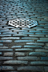 Vintage cobblestone street and manhole drain over