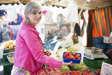 Frau kauft Erdbeeren auf dem Markt,