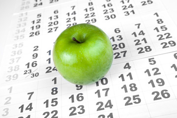 green apple on sheets of wall calendar