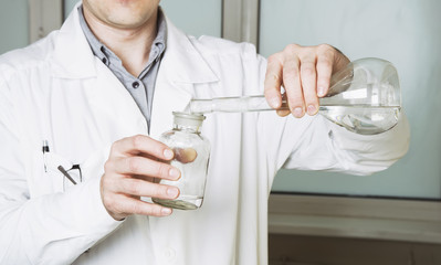 Laboratory assistant pours liquid from a flask