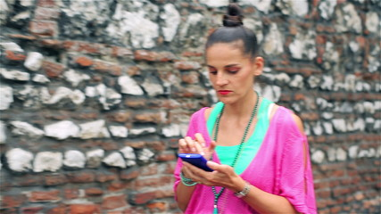 Woman with cellphone walking along brick wall, stedicam shot