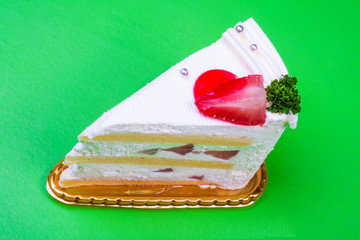 Strawberry cream cake in green background