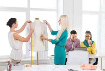 fashion designers measuring jacket on mannequin