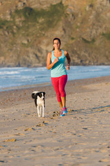 Sporty woman and dog running at beach