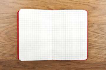 Notebook with square grid on wooden table.