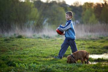 boy with a ball walking dog