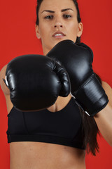 beautiful woman with the black boxing gloves, against the red ba