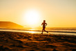 Female athlete running on sunset at beach