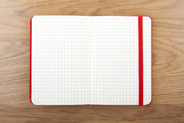 Notebook with elastic band on wooden background.