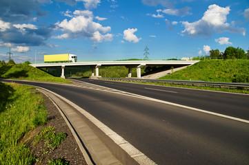 Bridge over an empty highway, going over the bridge truck