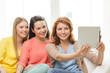 three smiling teenage girls with tablet pc at home