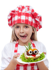 Happy little girl with chef hat and creative sandwich