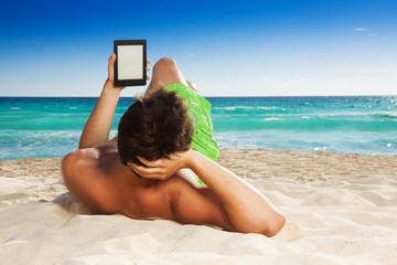 Man relaxing on beach reading e-book