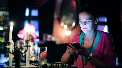 Portrait of smiling woman with laptop sitting in a pub, steadyca