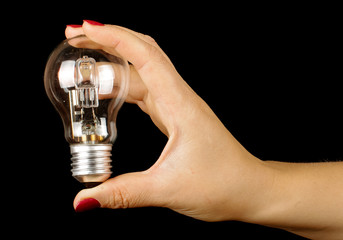 Female hand holding lamp isolated on the black background