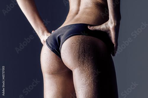 Tuinposter Gymnastiek female athlete rear view, trained buttocks