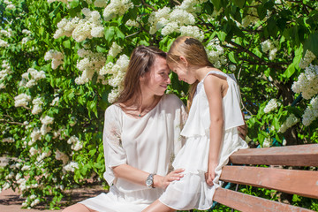 Happy mother and adorable girl enjoying warm day in lush garden