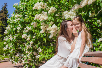 Young mother and adorable daughter whispering on the bench
