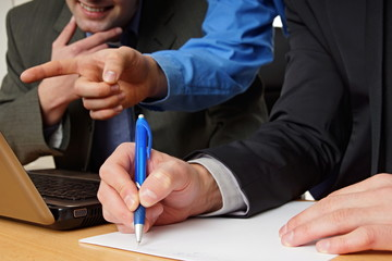 Businessman in suit writes document with other colleagues