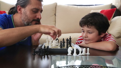 Father and son playing chess at home